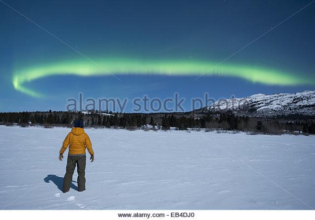 Ein Mann, einen Blick auf das Nordlicht oder Aurora Borealis, über eine verschneite Landschaft genießen. Stockbild