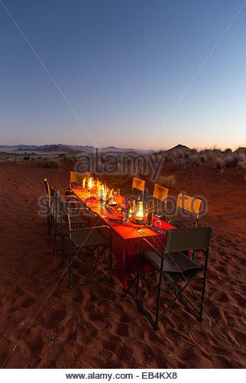 Ein romantischer Tisch beleuchtet mit Laternen in eine Wüstenlandschaft der Macchia-Vegetation und Mittelgebirge. Stockbild