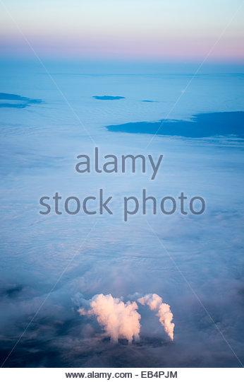 Luftaufnahmen von rosa Sonnenaufgang Licht leuchtenden Rauch aus Schornsteinen auf einem Hintergrund von Bodennebel Stockbild