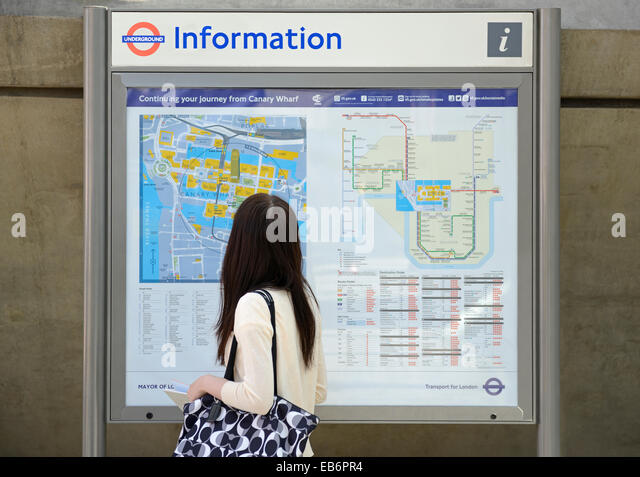 Woman Looking at einen Stadtplan mit Travel Information, Canary Wharf, London, UK. Stockbild