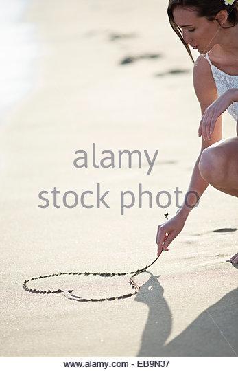 Herz der Frau-Zeichnung auf Sand Stockbild
