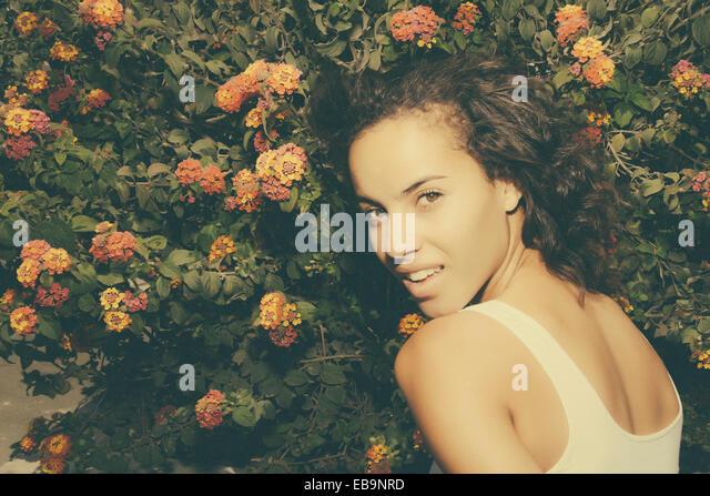 Junge Frau stand vor blühenden Busch Stockbild