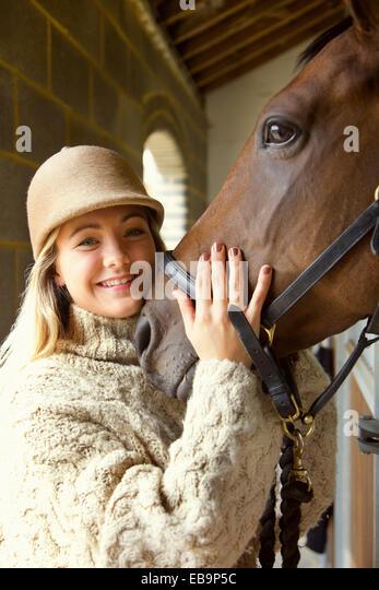 Lächelnde junge Frau streicheln Pferdekopf Stockbild