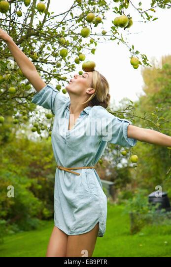 Frau im Obstgarten Balancing Apple auf der Stirn Stockbild