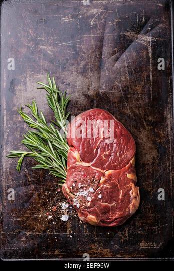 Rohes Frischfleisch Ribeye Steak und Rosmarin auf dunklem Hintergrund Stockbild