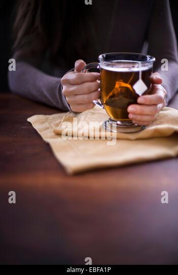 Frau hält eine Tasse heißen Tee sitzen auf Leinen und dunklen Oberfläche des Holzes. Dunklen Morgen Stockbild