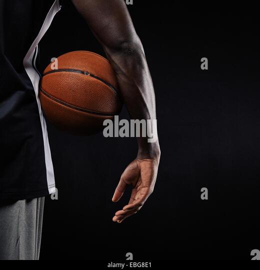 Nahaufnahme eines Basketballs in der Hand eines jungen afrikanischen Athleten vor schwarzem Hintergrund mit Textfreiraum. Stockbild