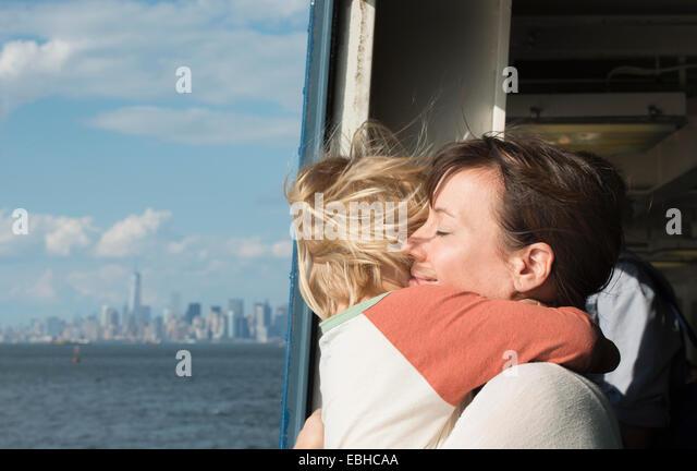 Mutter umarmt Sohn auf Boot Stockbild