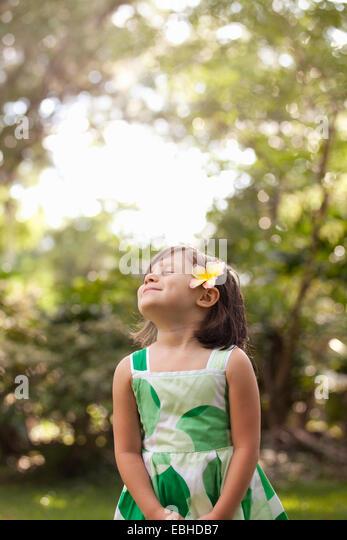 Junges Mädchen im Garten, Blume im Haar tragen Stockbild
