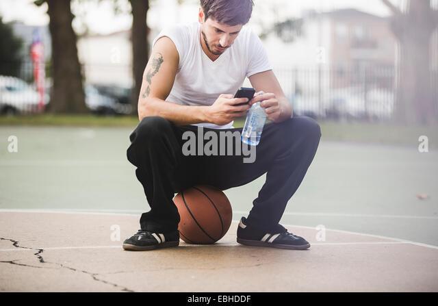 Junge männliche Basketball sitzend auf Kugel SMS auf smartphone Stockbild
