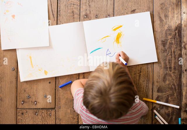 Junge, Zeichnung auf Papier, hoher Winkel Stockbild