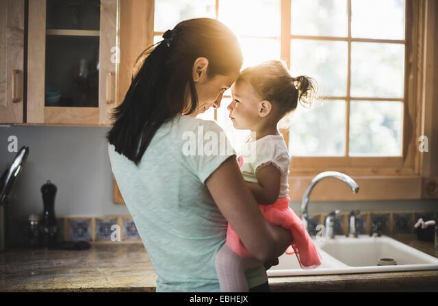 Mutter und Tochter spielen in Küche Stockbild