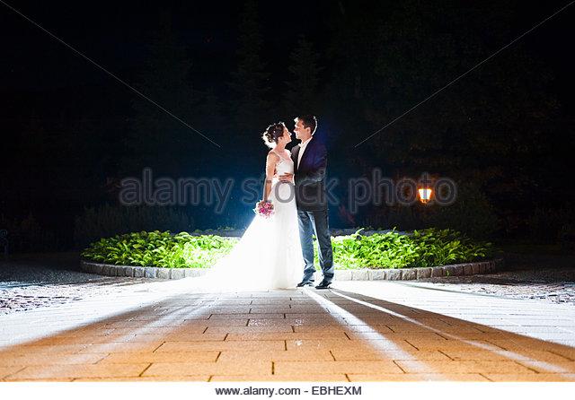 Romantische Frischvermählten Mitte erwachsenes paar im Garten nachts beleuchtet Stockbild