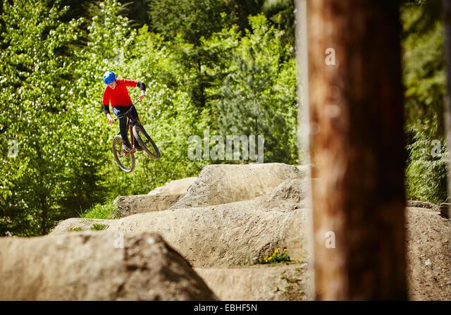 Junge weibliche bmx-Biker springen Luft aus Felsen im Wald Stockbild
