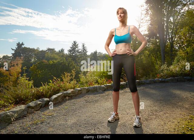 Porträt von weiblichen Läufer mit Händen auf den Hüften im park Stockbild