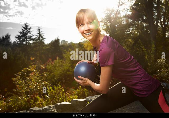 Mitte Erwachsene Frau mit Gymnastikball im park Stockbild