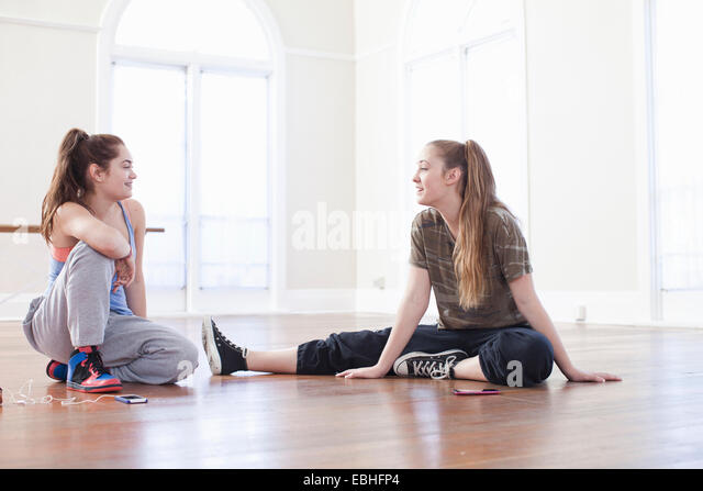 Zwei Mädchen im Teenageralter sitzen am Boden im Chat in der Ballettschule Stockbild
