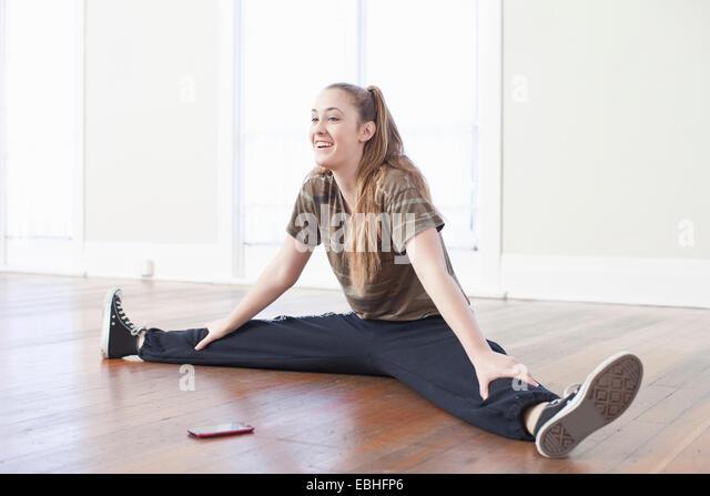 Teenager-Mädchen Aufwärmen und dabei den Spagat in der Ballettschule Stockbild