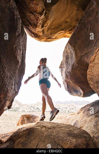 Frau balancieren auf Felsen, Joshua Tree Nationalpark, Kalifornien, USA Stockbild