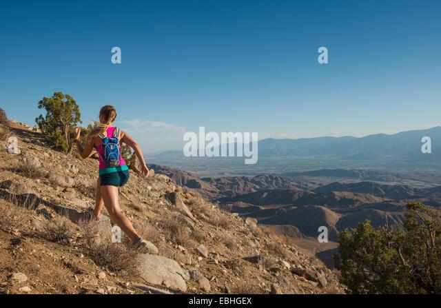 Frau läuft auf Berg, Joshua Tree Nationalpark, Kalifornien, USA Stockbild