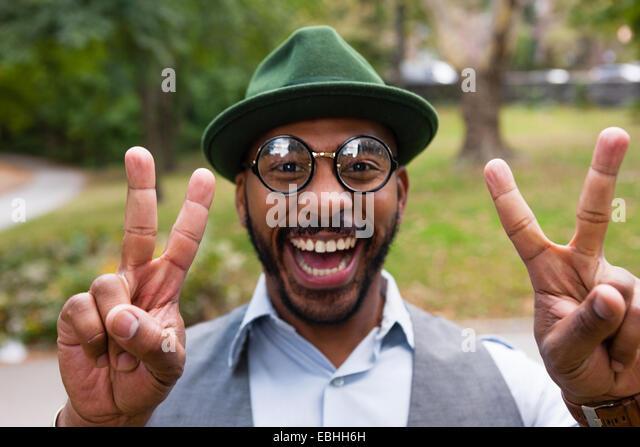 Mann die Peace-Zeichen breit lächelnd in park Stockbild