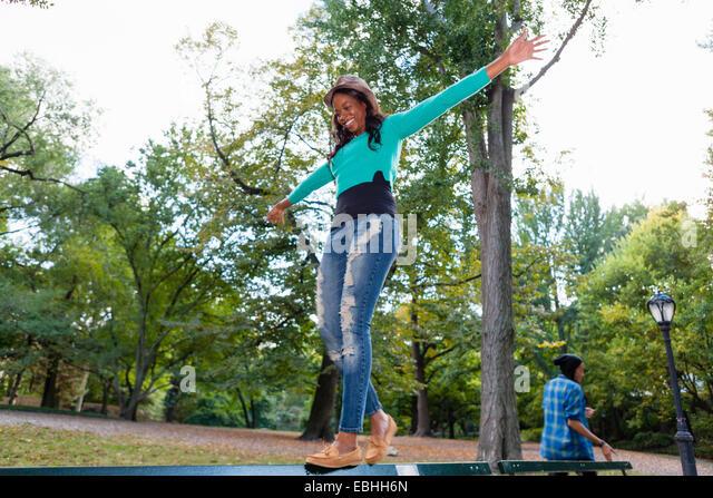 Frau balancieren auf Geländer im park Stockbild