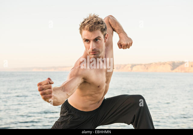 Mitte erwachsener Mann am Strand in Kung-Fu-pose Stockbild