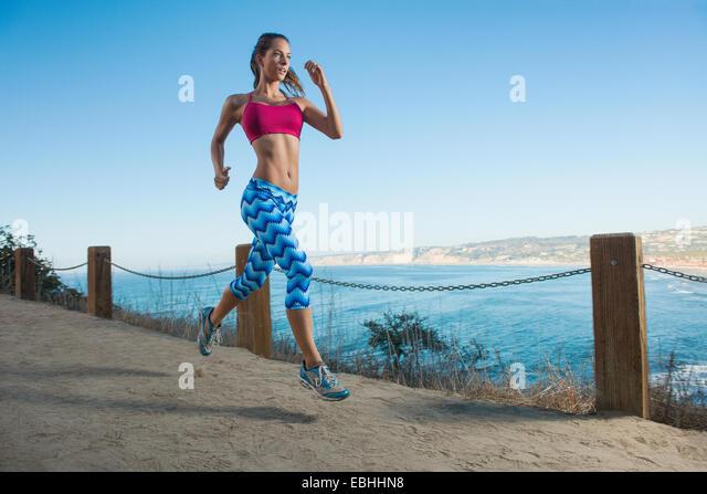 Junge Frau läuft Weg auf dem Seeweg Stockbild