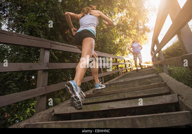 Mitte erwachsenen Mann und junge Frau angerannt Schritte, hinten, niedrigen Winkel Ansicht Stockbild