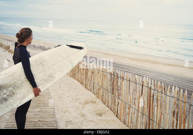 Surfer mit Surfbrett am Strand, Lacanau, Frankreich Stockbild