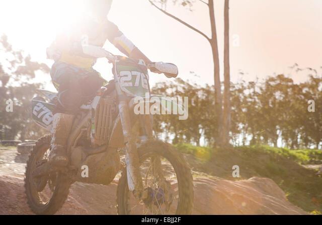 Zugeschnittenen Schuss von jungen männlichen Motocross Racer Luft Schlamm Hügel hinunter springen Stockbild