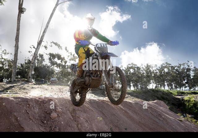 Junge männliche Motocross Racer Luft Schlamm Hügel hinunter springen Stockbild
