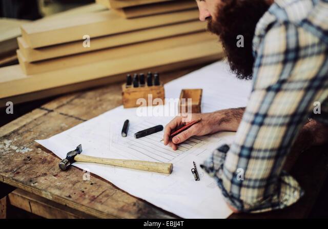 Schuss von Mitte adult Handwerker blickte auf Blaupause im Orgelwerkstatt beschnitten Stockbild