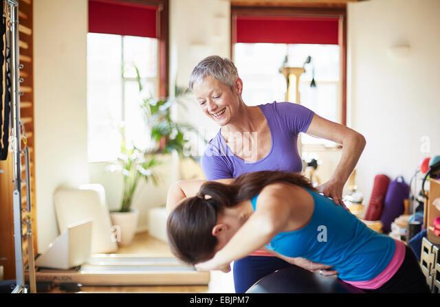 Junge weibliche Schüler und Lehrer mit Pilates Barrel im Pilates-Fitness-Studio Stockbild