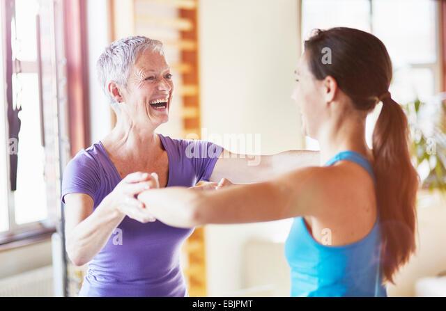 Junge Schülerin mit Lehrer in Pilates Turnhalle lachen Stockbild
