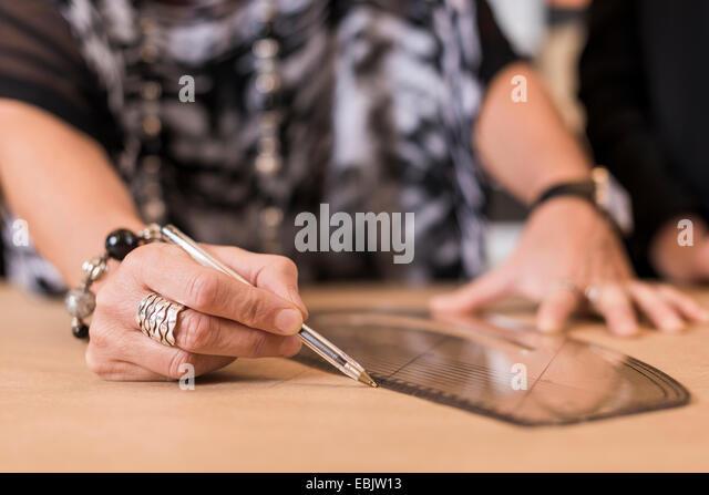 Nahaufnahme von Reifen Näherin zeichnen mit gebogenen Herrscher auf Schneiderinnen Muster in Werkstatt Stockbild