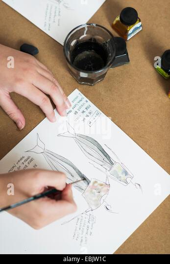 Junge Womans Hände malen Modedesign auf Arbeitstisch Stockbild