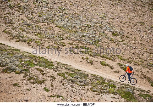Männliche Mountainbiker Radfahren, steilen Feldweg, Tal Reykjadalur, South West Island Stockbild