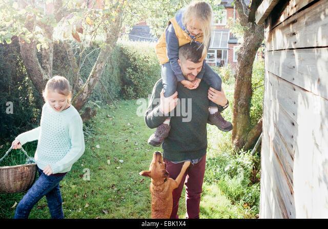 Vater mit Tochter auf Schultern im Garten Stockbild