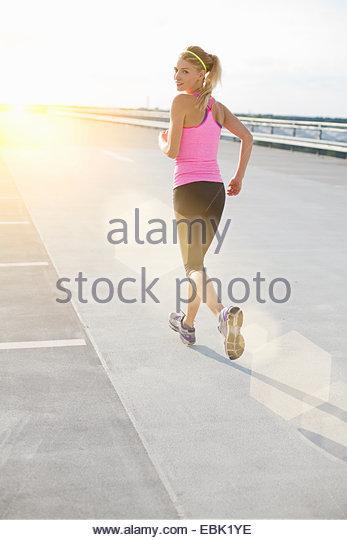 Junge Frau, jogging, über die Schulter schauen Stockbild