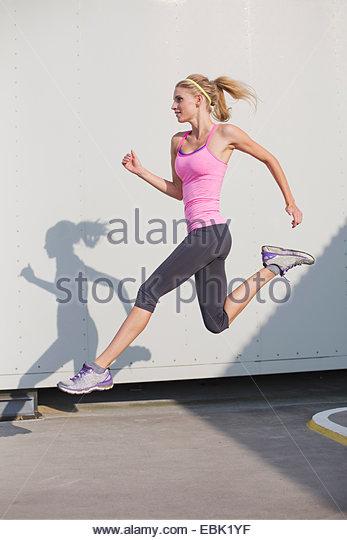 Junge Frau laufen und springen Stockbild