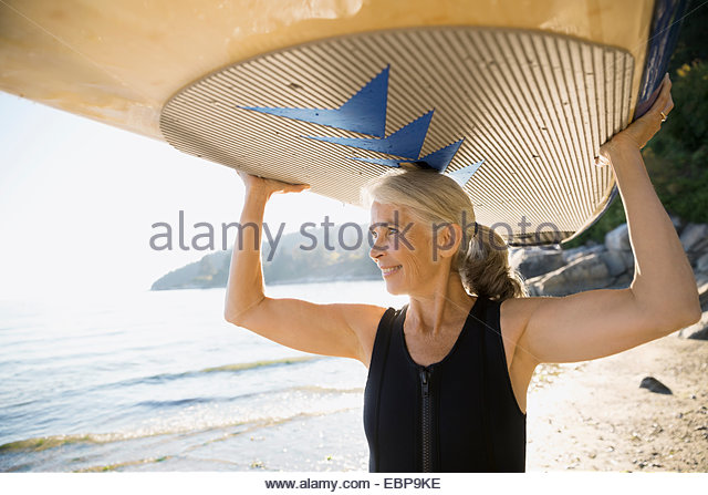 Ältere Frau hält Paddle Board overhead am Strand Stockbild