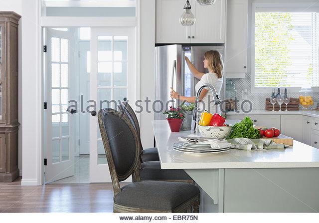 Frau Gefrierschrank Tür in Küche Stockbild