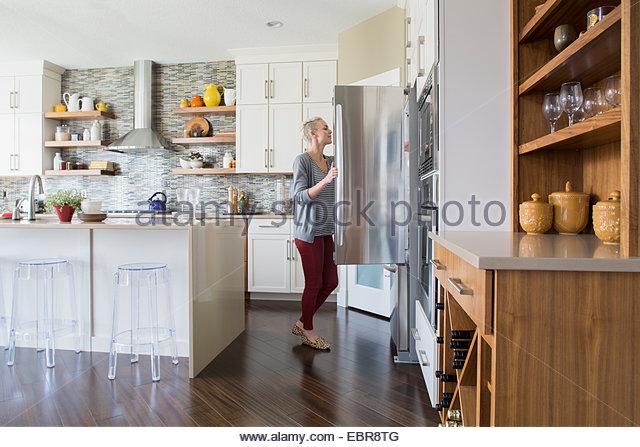 Frau, die Kühlschranktür zu öffnen, in der Küche Stockbild
