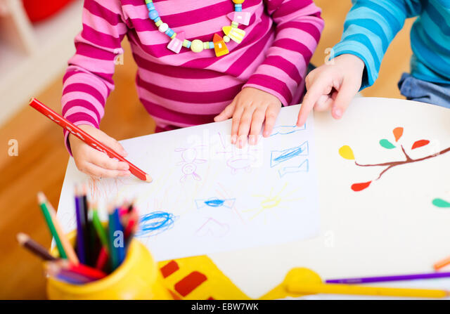 zwei kleine Kinder zeichnen mit Buntstiften Stockbild