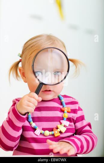 ein kleines Mädchen Blick durch eine Lupe Stockbild