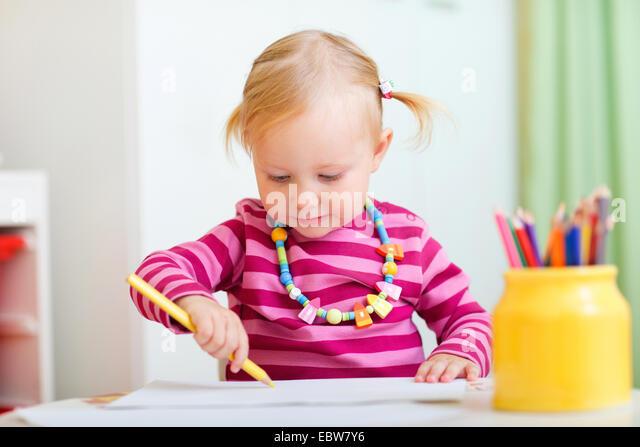 kleines Mädchen zeichnen mit Buntstiften Stockbild