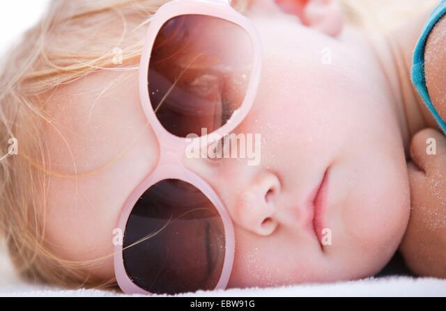 kleines Mädchen schlafen am Strand, Porträt Stockbild