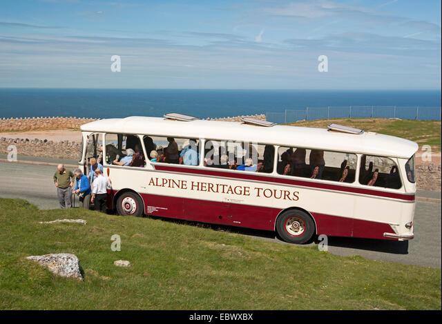 Heritage tour Bus / bus mit ältere Passagiere aussteigen auf Great Orme mit blauen Ozean im Hintergrund an Stockbild