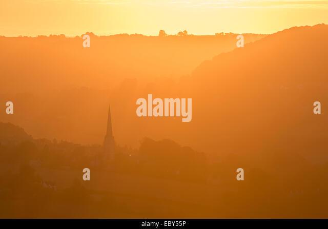 Painswick Kirche in den Cotswolds bei Sonnenaufgang an einem nebligen Morgen, Gloucestershire, England. Herbst (September) Stockbild